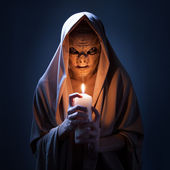 Warlock with candle in darkness. — Stock Photo