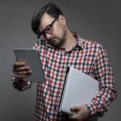 Handsome hipster busy man with many gadgets in hands. — Stock Photo