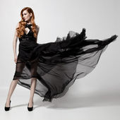 Fashion woman in fluttering black dress. White background. — Stock Photo