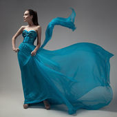 Fashion woman in fluttering blue dress. Gray background. — Stock Photo