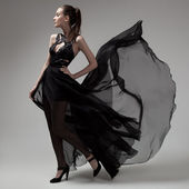 Fashion woman in fluttering black dress. Gray background. — Stock Photo
