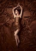 Beautiful woman lying on a chocolate fabric. — Stockfoto