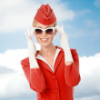 Charming Stewardess Dressed In Red Uniform And Vintage Sunglasse — Stock Photo #57569795