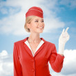 Charming Stewardess Dressed In Red Uniform Pointing The Finger. — Stock Photo #57569797