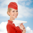 Charming Stewardess Holding Paper Plane In Hand. Sky With Clouds — Stock Photo #57569809
