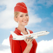 Charming Stewardess Holding Airplane In Hand. Sky With Clouds Ba — Stock Photo #57569823