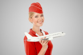 Charming Stewardess Holding Airplane In Hand. Gray Background. — Stock Photo