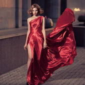 Young Beautiful Woman In Fluttering Red Dress. City Background. — Stock Photo