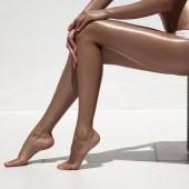 Beautiful woman tan legs. Against white wall. — Stock Photo