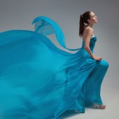 Beautiful woman in fluttering airy blue dress. Gray background. — Stock Photo