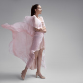 Beautiful woman in fluttering airy pink dress. Gray background. — Stock Photo