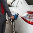 Male hand pumping petrol into car, refueling with nozzle at gas — Stock Photo #77724632
