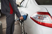 Male hand pumping petrol into car, refueling with nozzle at gas — Stock Photo