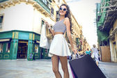 Girl dressed in a fashionable way doing shopping — Stock Photo