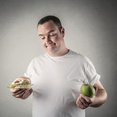 Chubby man deciding whether to eat healthy food or a hamburger — Stock Photo