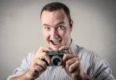 Chubby man holding an old-fashioned camera — Stock Photo