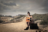 Girl playing guitar on a dusty road — Stock Photo