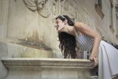 Young thirsty girl drinking water from a fountain — Foto Stock