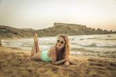 Beautiful blonde girl lying in the sand at sunset — Stock Photo