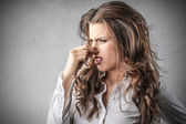 Businesswoman looking disgusted and holding her nose — Stock Photo