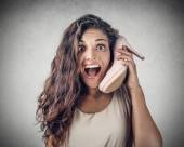Young surprised girl using a shoe instead of a mobile phone — Stock Photo