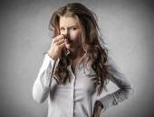 Disgusted young woman holding her nose — Stock Photo
