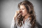 Beautiful woman looking disgusted by a bad smell — Foto Stock