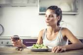 Young girl deciding whether to eat a healty salad or a muffin — Stock Photo