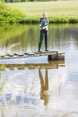 Genç kadın gölet iskelede balık tutma — Stok fotoğraf