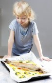 Portrait of little girl with baked trout salmon — Stock Photo