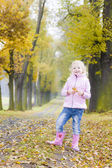 Little girl wearing rubber boots in autumnal alley — Stock Photo