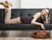 Woman wearing pumps with a handbag lying on sofa — Stock Photo