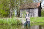 Woman fishing in pond in spring — Stock Photo