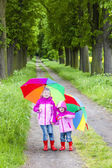 Little girls wearing rubber boots with umbrellas in spring alley — Stock Photo