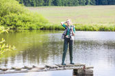 Young woman fishing on pier at pond — Stock Photo
