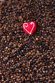 Still life of coffee beans and marzipan heart — Stock Photo