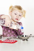 Little girl playing with child dish — Stockfoto
