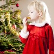 Little girl as Santa Claus by Christmas tree — Stock Photo #56300357