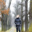 Woman wearing black clothes and boots in autumnal alley — Stock Photo #56303757