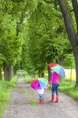 Matki i córki z parasolami w wiosna zaułek — Zdjęcie stockowe