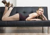 Woman lying on sofa — ストック写真