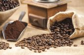 Still life of coffee beans in jute bags with coffee grinder — Stock Photo