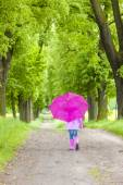 Little girl wearing rubber boots with umbrella in spring alley — Stock Photo
