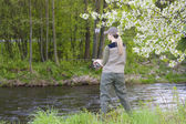 Woman fishing by the river in spring — Stock Photo