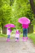 Mother and her daughters with umbrellas — Stock Photo