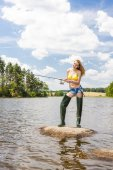 Woman fishing in pond during summer — Stock Photo