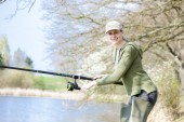 Woman fishing at pond in spring — Stock Photo