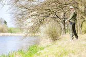 Woman fishing at pond in spring — Stock fotografie