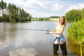 Young woman fishing in pond during summer — Stock Photo