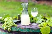 Wine glass and carafe with wine cider standing on cask — Stock Photo
